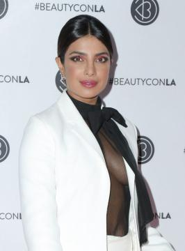 Priyanka Chopra stuns in white suit and sheer black top Priyanka Chopra Jonas attends Beautycon Los Angeles 2019 Pink Carpet in white suit and sheer black top